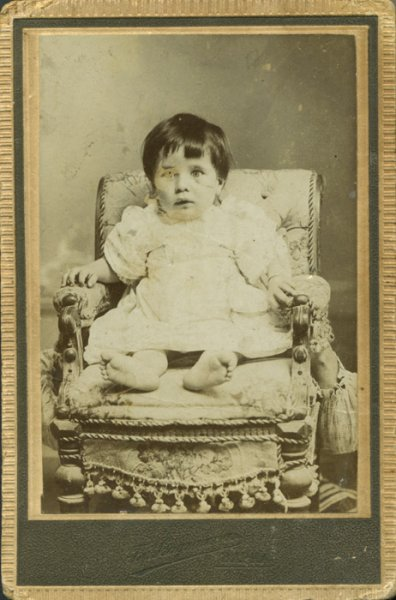 Studio portrait of a child in armchair