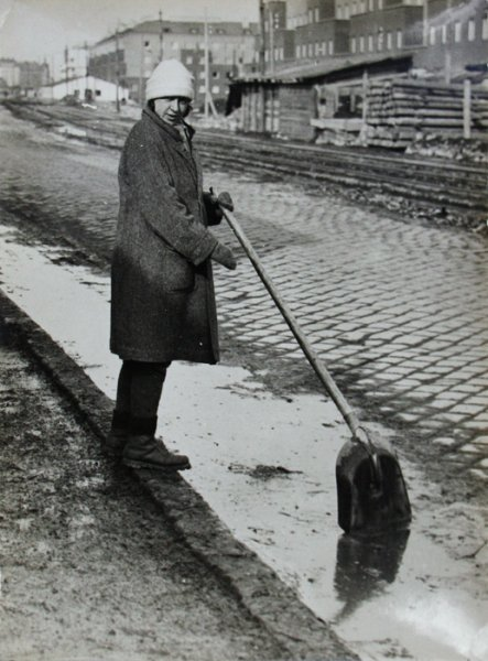 Untitled (woman cleaning sidewalk)