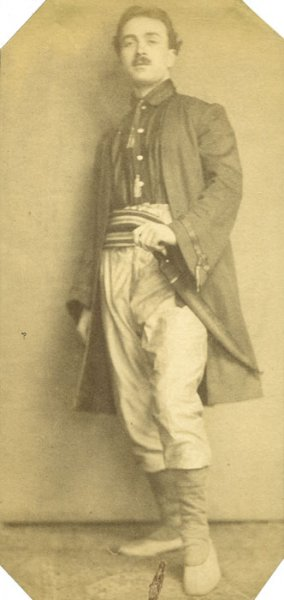 Portrait of a young man in traditional dress with a dagger