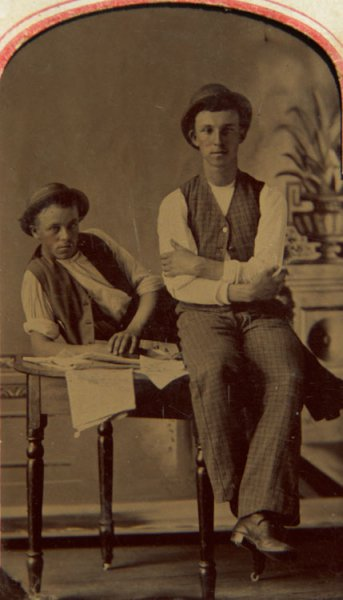 Untitled (studio portrait of two young men sitting on a table)