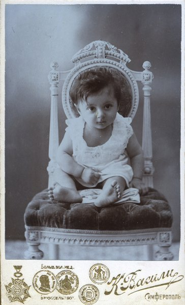 Untitled (portrait of a child on an ornate chair)