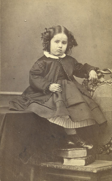 no title (studio portrait of a girl sitting on a table)